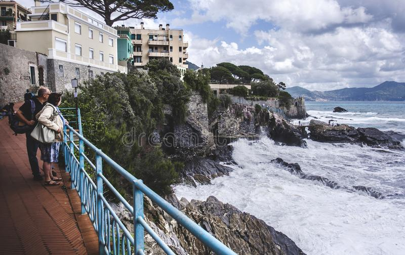 Genoa Nervi - l'Italia, - rocce tempestose della scogliera della costa di mare delle coppie senior fotografia stock