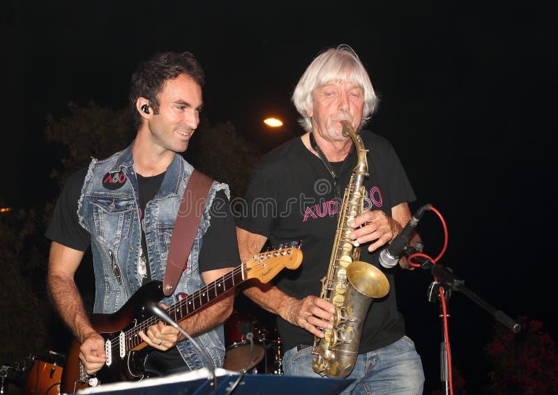 Genoa Pegli 6 Juli 2019: saxofonisten och gitarristen av den musikaliska gruppen 'ljudsignal 80' under en conof ljudsignal 80' fö royaltyfria foton
