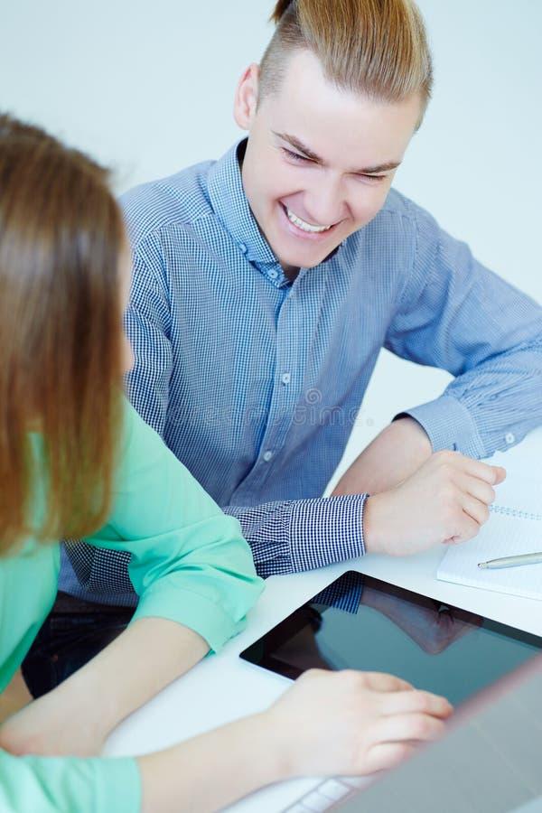 Genoegen van het werk samen Glimlachende partners die tablet en het bespreken van nieuw startproject gebruiken royalty-vrije stock afbeelding