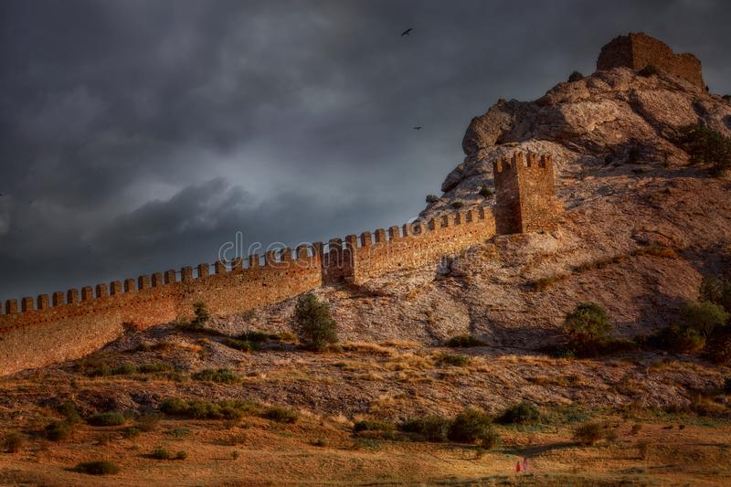 Genoese castle under dark sunset sky. Sudak Genoese  Castle in Crimea at summer evening with cloudy sky royalty free stock photos