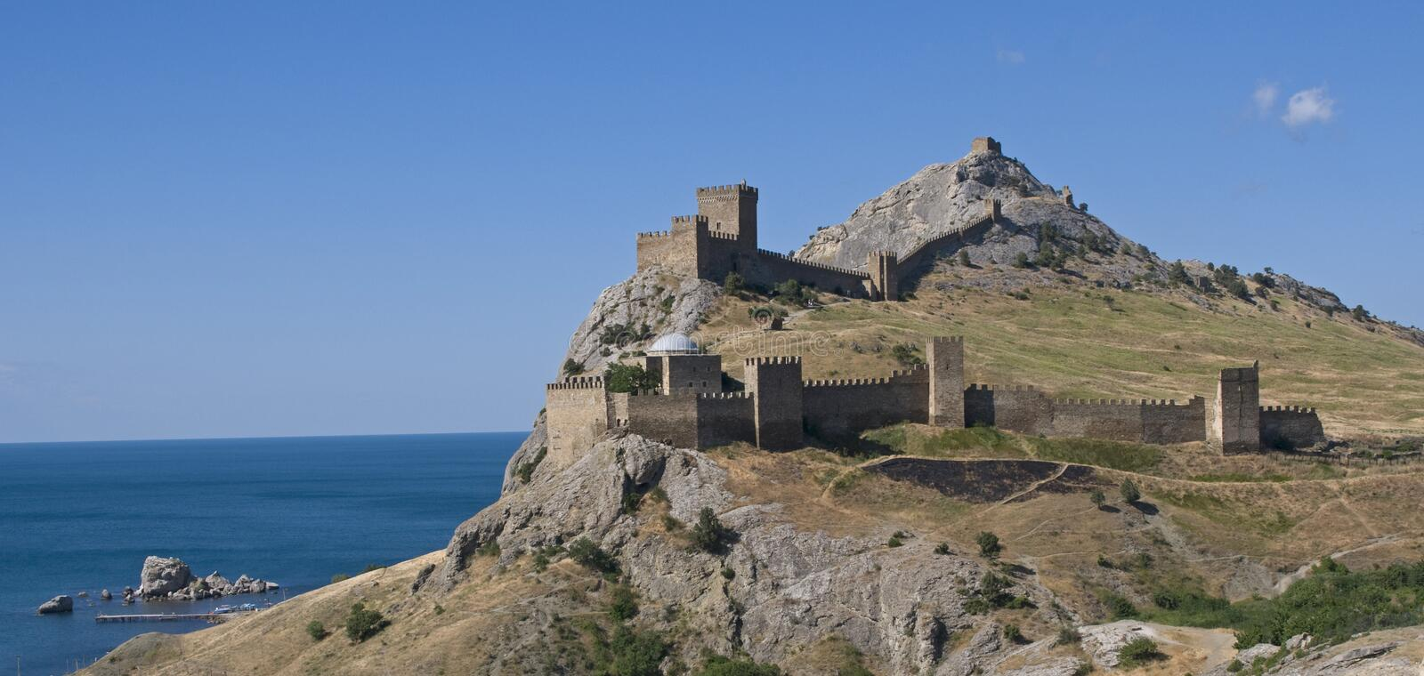 Genoese Sudak Castle. This is a Genoese Sudak Castle, Crimea. The Genoese fortress is situated on the rock against the blue sky and sea background royalty free stock image