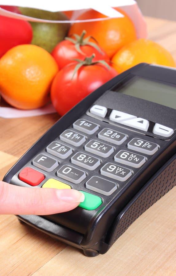 Genom att använda betalningterminalen, skriver in frukter och grönsaker, cashless betala för att shoppa, nummer för personligt ID royaltyfria bilder