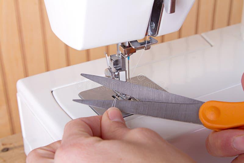 Använda sax för att klippa tråden på symaskinen arkivfoton