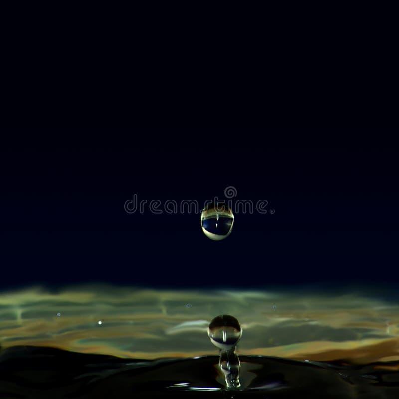 Genomblöt flytande, en droppe av vatten bildade en liten pelare fotografering för bildbyråer