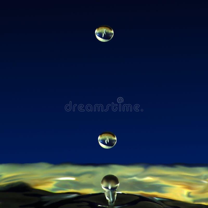 Genomblöt flytande, två droppar av vatten lyftte pelaren royaltyfria bilder