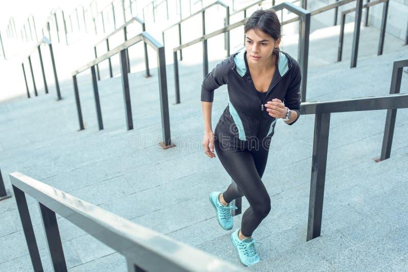 Genomkörare för aktiv övning för ung kvinna på den utomhus- gatan royaltyfri foto