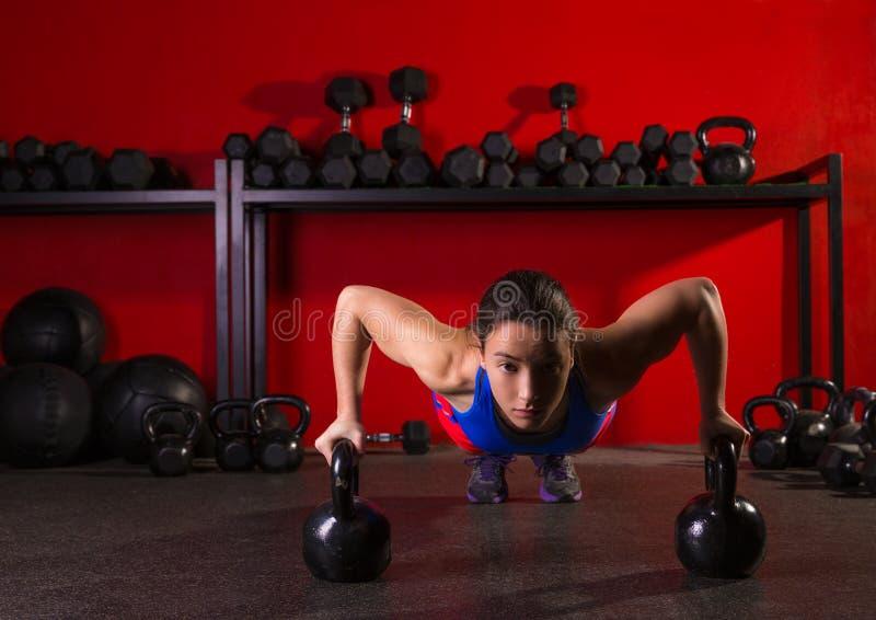 Genomkörare för idrottshall för styrka för Kettlebells liggande armhävningkvinna arkivbild