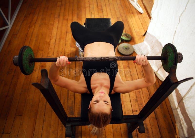 Genomkörare för konditionkvinnautbildning som gör squats med skivstången i idrottshall royaltyfri foto