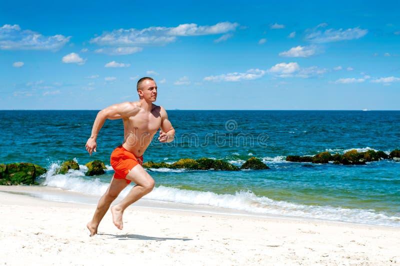 genomkörare Idrotts- manspring på stranden fotografering för bildbyråer