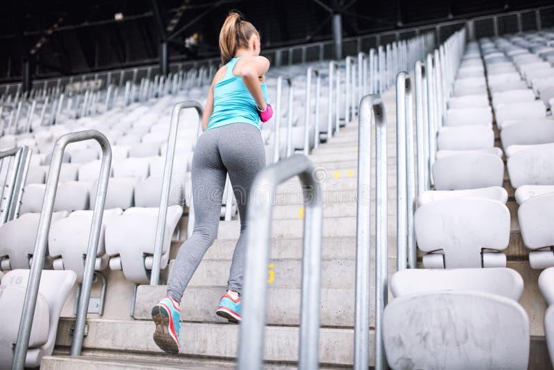 Genomköraren på stadion, den sunda kvinnlign som gör kondition, övar Kvinnlig spring på trappa royaltyfri foto