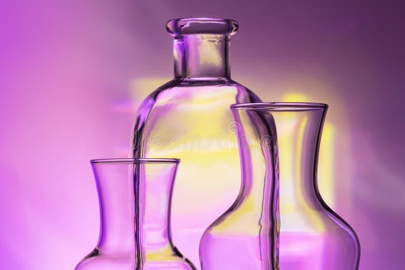 Genomskinlig bordsservis för exponeringsglas - flaskor av olika format, tre stycken på härligt mång--färgat, gult, lila och royaltyfria foton