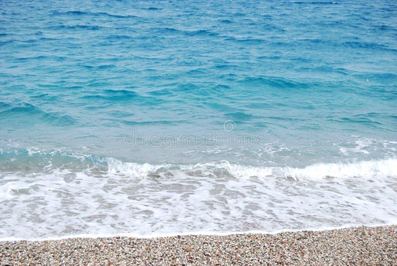 Genomskinlig djupblå våg av havet som bryter på kusten w arkivfoto