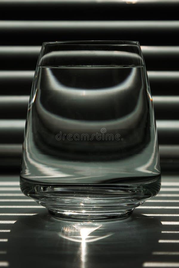 Genomskinlig exponeringsglaskopp med klart vatten mot bakgrunden av en randig skärm med strålar av ljus Mall orientering, bakgrun arkivfoton