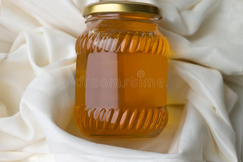 Genomskinlig honung i en exponeringsglaskrus ligger på bordduken arkivbild