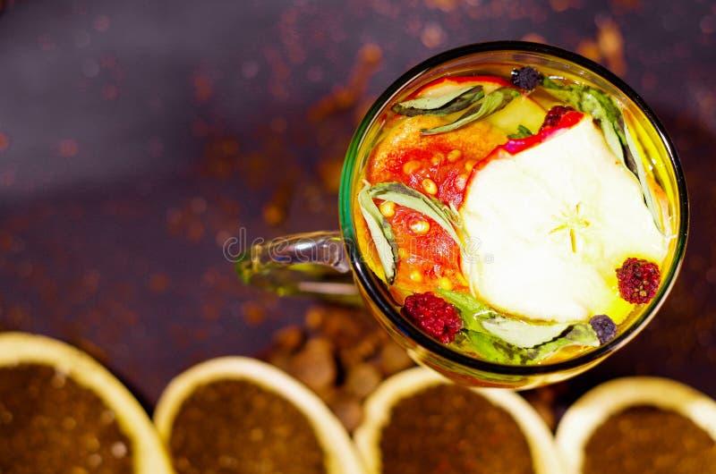 Genomskinlig kopp av avkokte med färgrikt växt- val inom, härligt ordnings-, te- och örtbegrepp arkivfoton