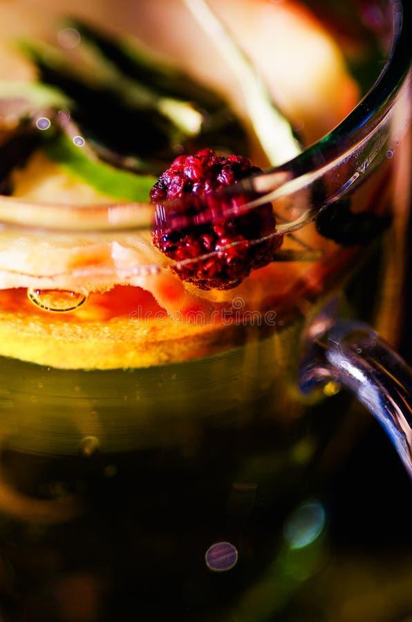 Genomskinlig kopp av avkokte med färgrikt växt- val inom, härligt ordnings-, te- och örtbegrepp arkivfoto