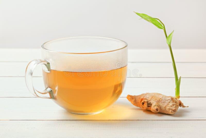 Genomskinlig kopp med varmt te som är vått från ånga på exponeringsglas, torr ginge arkivbild