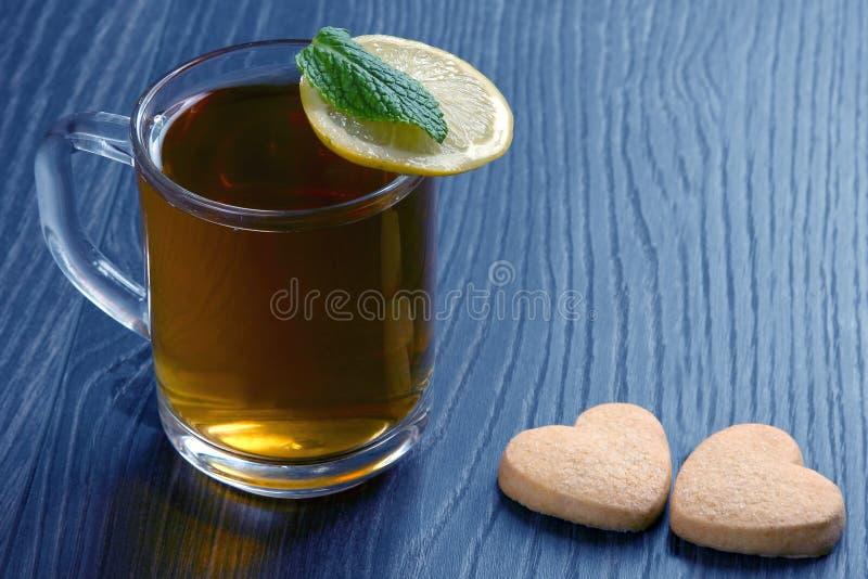 Genomskinlig kopp te med citronen, mintkaramellen och kakor på en trätabell royaltyfri bild
