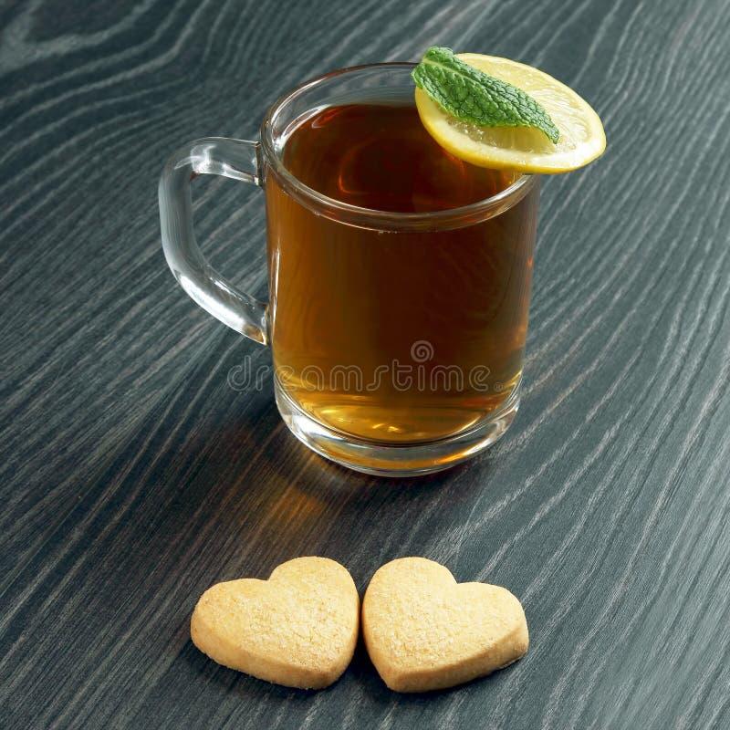 Genomskinlig kopp te med citronen, mintkaramellen och kakor på en trätabell royaltyfri fotografi