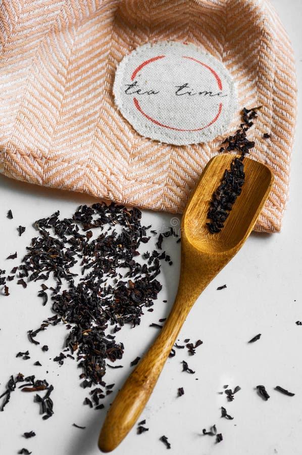Genomskinlig kopp te som bryggas med närgränsande träskedar hel kanel porslinet besegrar ny tid för porslinjordgubbetea Teblad, l royaltyfria bilder