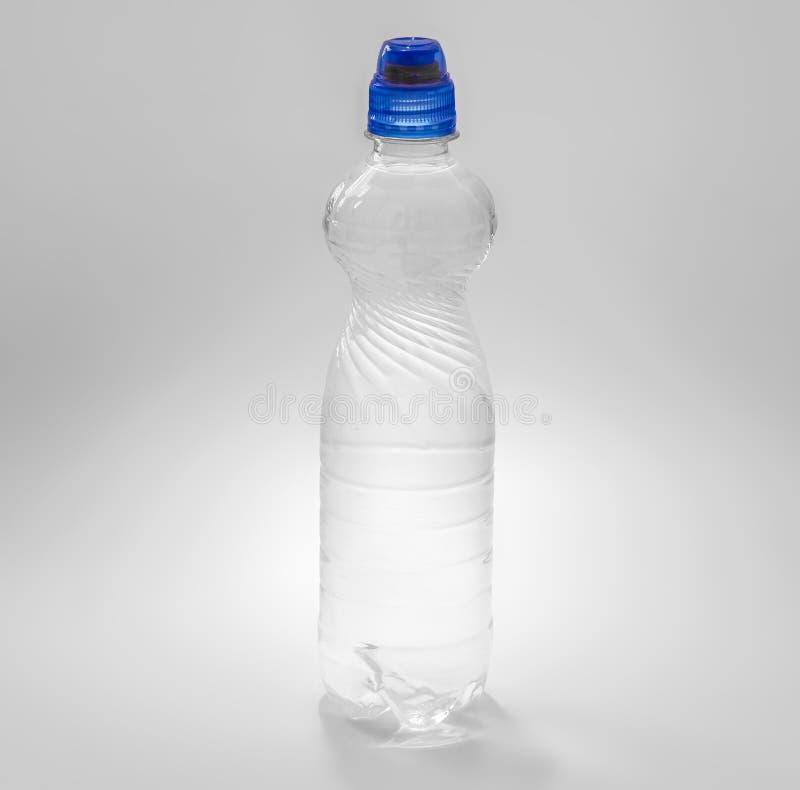 Genomskinlig plast- flaska med en blå kork med en supare som fylls med vatten arkivbilder