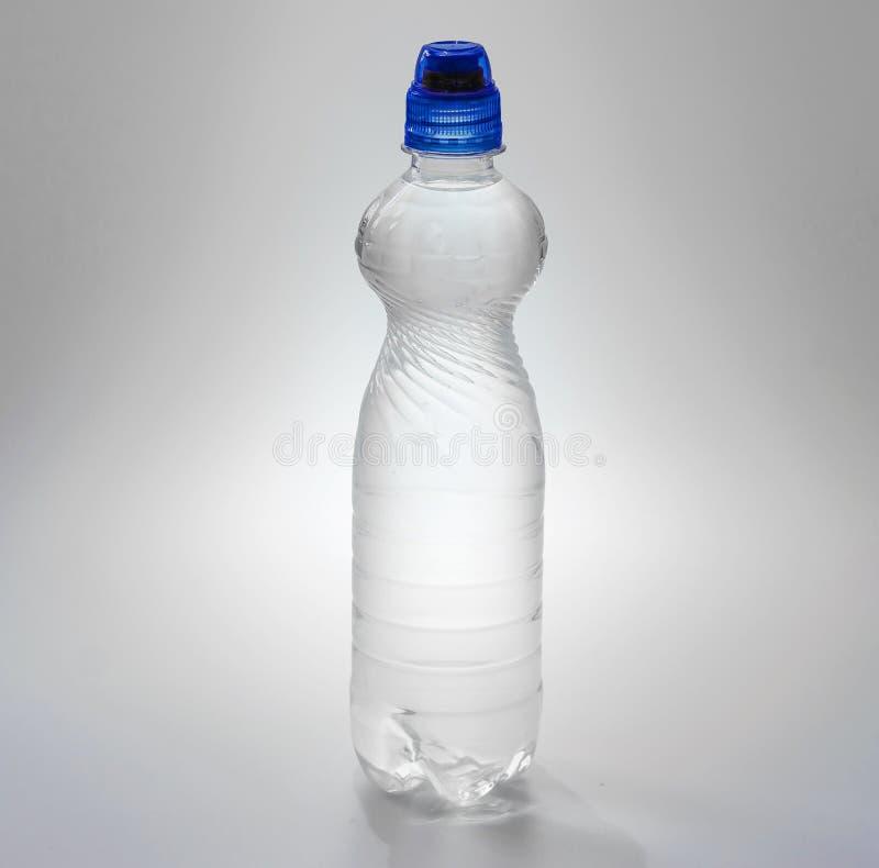Genomskinlig plast- flaska med en bl? kork med en supare som fylls med vatten arkivfoto