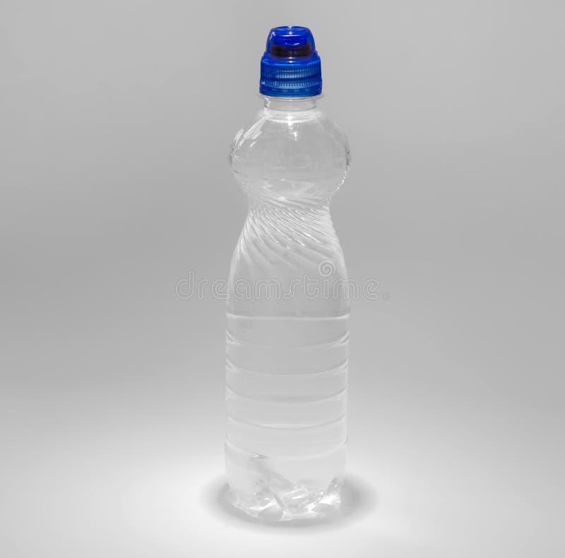 Genomskinlig plast- flaska med en bl? kork med en supare som fylls med vatten arkivbild