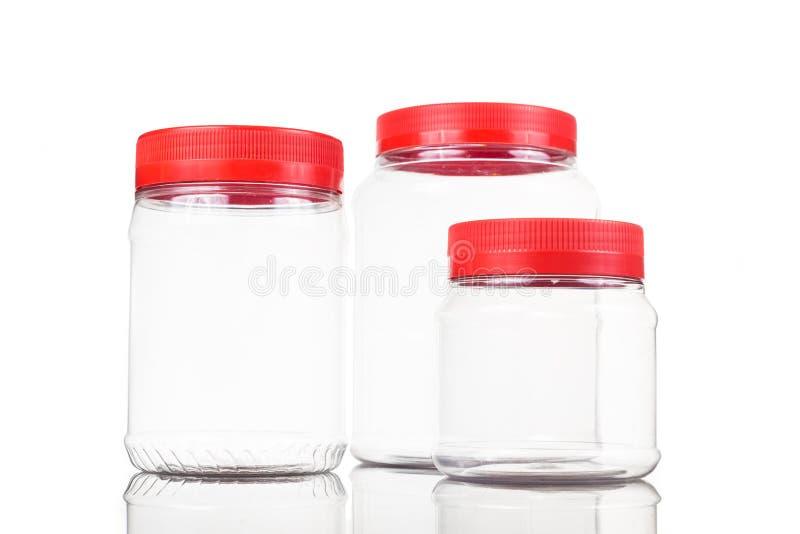 Genomskinlig plast-PVC-krus med den röda räkningen som isoleras i vit royaltyfria foton