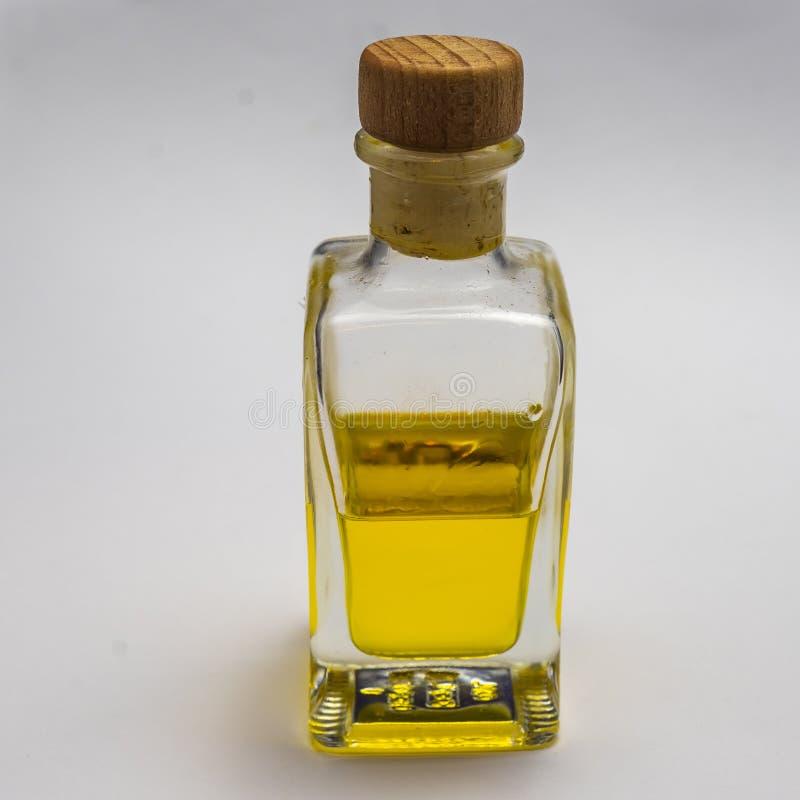 Genomskinlig rektangulär glasflaska med en korkpropp Halva som fylls med en gul lysande flytande, synlig mot en vit backg arkivbilder