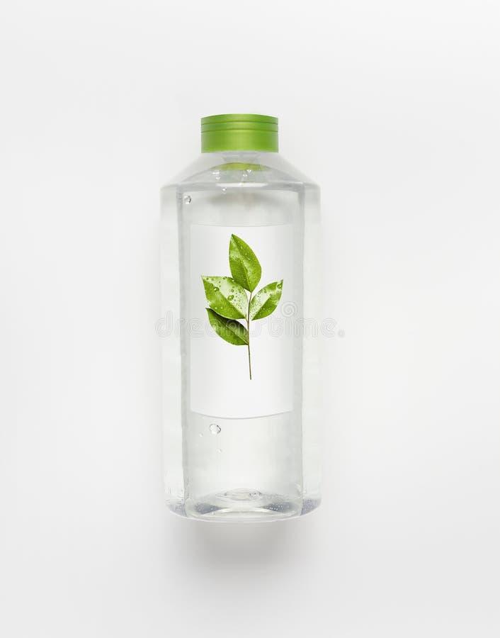 Genomskinlig vätskeflaska med det gröna locket Rent naturvatten med gräsplansidor och brännmärkaåtlöje upp på det vita skrivborde royaltyfria foton