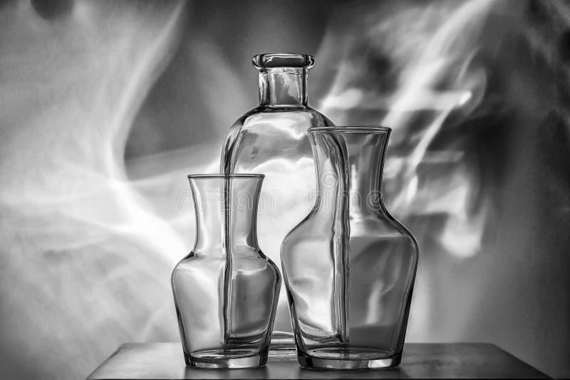 Genomskinliga bordsservis-flaskor för exponeringsglas av olika format, tre stycken på ett svartvitt foto mycket härlig stilleben arkivfoton