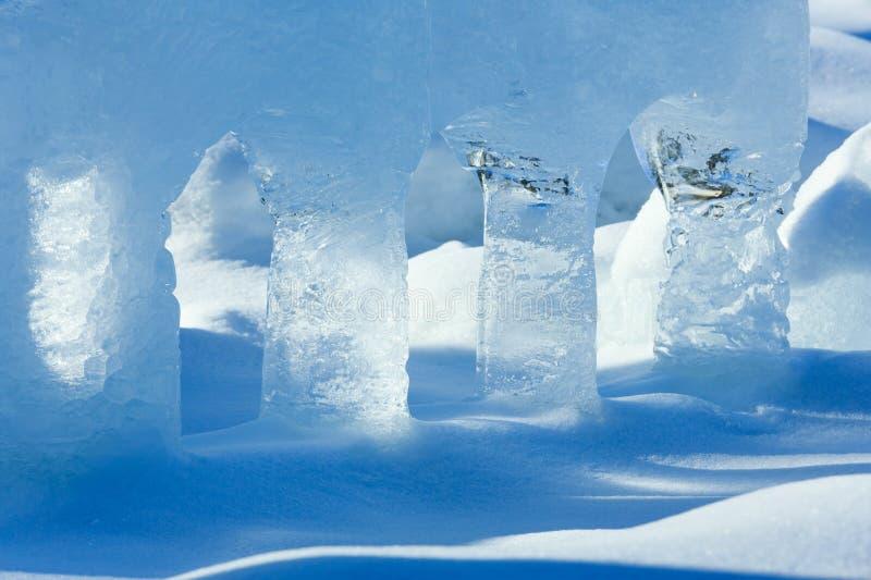 Genomskinliga kolonner av is på snön arkivbild