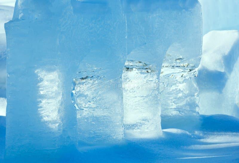 Genomskinliga kolonner av is på snön royaltyfri bild