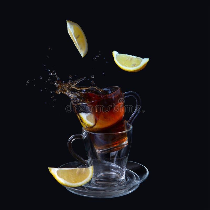 Genomskinliga koppar med te på en svart bakgrund Citronskivor faller in i koppen Bristningar färgstänk fotografering för bildbyråer