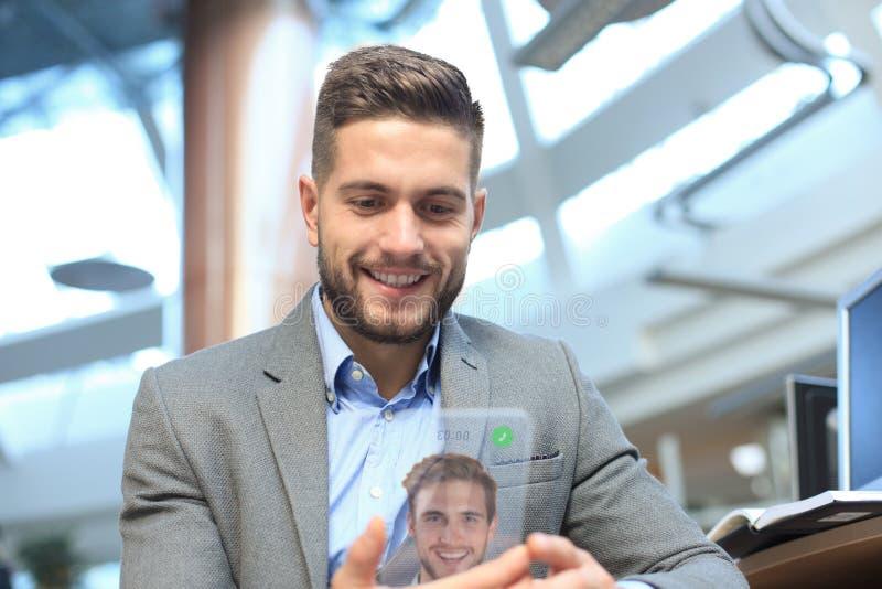 Genomskinliga telefoner av det framtida begreppet, en Caucasian affärsman som har en video appell med hans vän royaltyfri bild