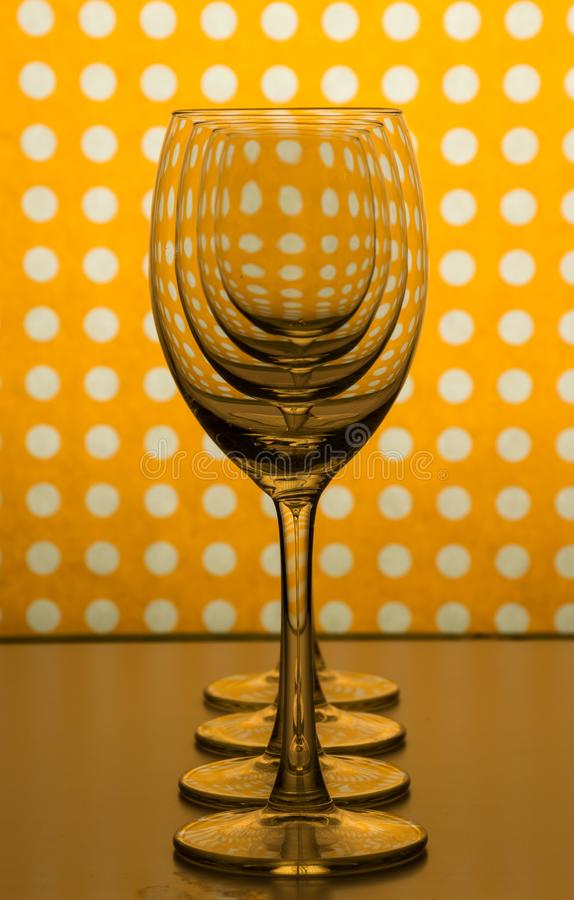 Genomskinliga tomma vinexponeringsglas ett bak annat och gul orange bakgrund med vita fläckar royaltyfri bild