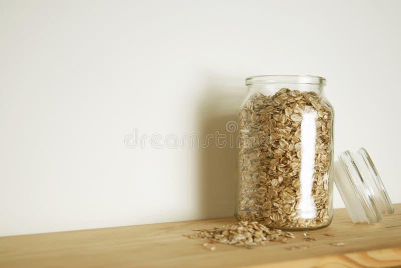Genomskinligt exponeringsglas med havremål i den glass kruset som isoleras isolerat på trätabellen Sund frukostingrediens royaltyfri fotografi
