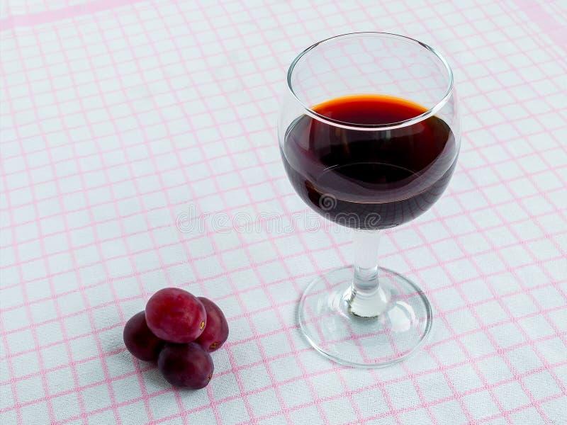 Genomskinligt exponeringsglas med rött vin och få söta röda druvor på den vita rosa bordduken Bekl?da besk?dar royaltyfri fotografi