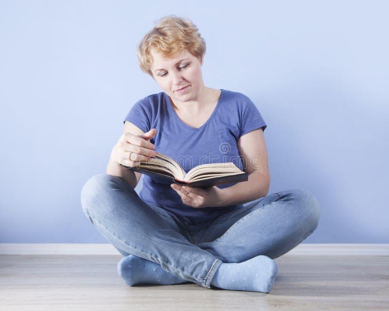 Genomsnittsålderkvinnasammanträde på golvet och läsningen royaltyfria bilder