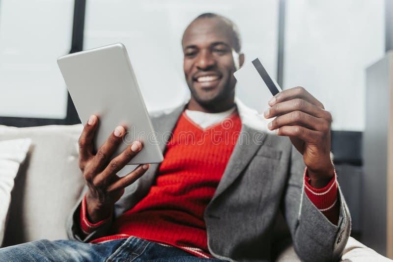 Genoten van mannelijke persoon die met tablet en bankkaart in handen rusten stock afbeelding