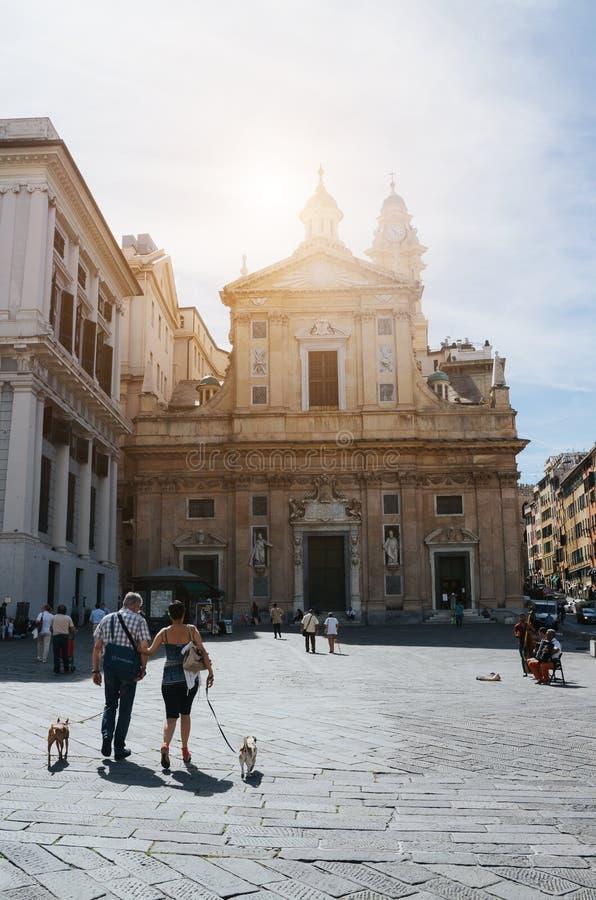 GENOVA, ITALIA - 21 GIUGNO 2016: Accoppi con due cani che camminano davanti al dei Santi Ambrogio la e Andrea, a di Chiesa del Ge fotografia stock libera da diritti