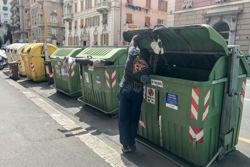 GENOVA, ITALIA - GIUGNO, 9 del 2017 - alimento di ricerca migratore dentro il contenitore di rifiuti dell'immondizia fotografia stock