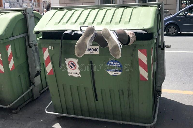 GENOVA, ITALIA - GIUGNO, 9 del 2017 - alimento di ricerca migratore dentro il contenitore di rifiuti dell'immondizia fotografie stock