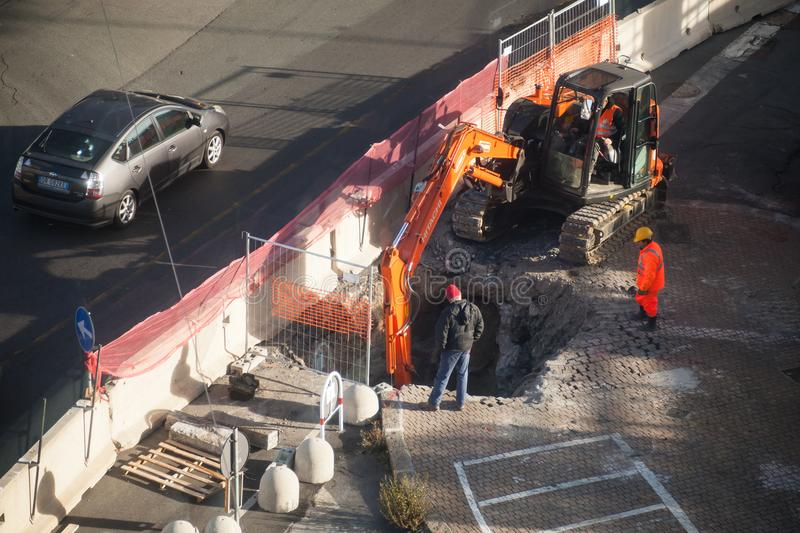 Workers dig hole in asphalt with excavator stock photography