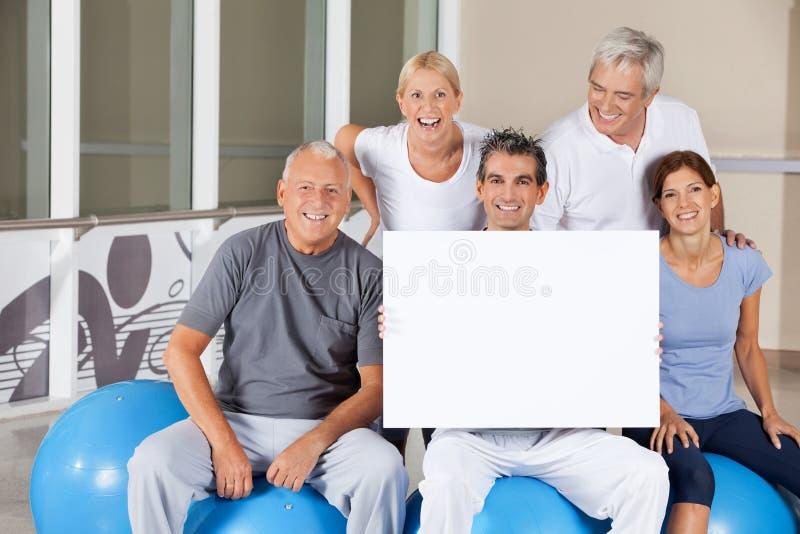 Gens aînés retenant l'affiche vide photographie stock libre de droits