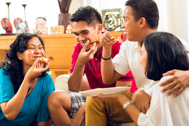Gens asiatiques mangeant de la pizza à la réception image stock