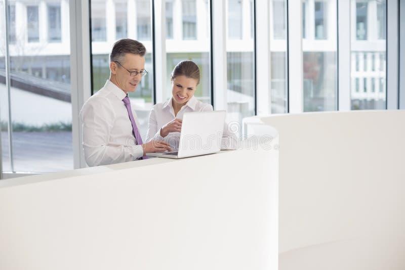 Gens d'affaires à l'aide de l'ordinateur portable sur la balustrade dans le bureau photographie stock