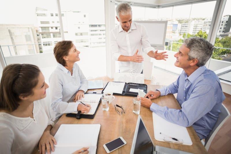 Gens d'affaires écoutant la présentation de collègues image stock