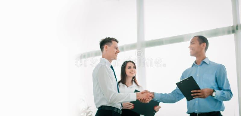 Gens d'affaires amicaux se serrant la main sur le fond brouill? images libres de droits