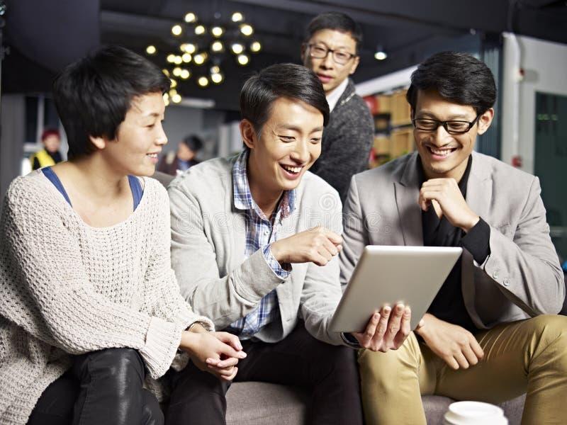 Gens d'affaires asiatiques à l'aide du comprimé dans le bureau photo stock
